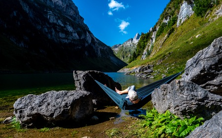 guy chilling in a hammock between two stones at a mountain lake enjoing the view switzerland alpstein Archivio Fotografico - 120999303