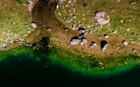 aerial top down view of guy chilling in a hammock between two stones at a mountain lake, switzerland Archivio Fotografico - 120999307