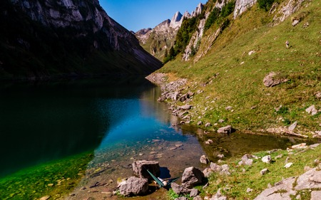 aerial view of guy chilling in a hammock between two stones at a mountain lake enjoing the view switzerland alpstein