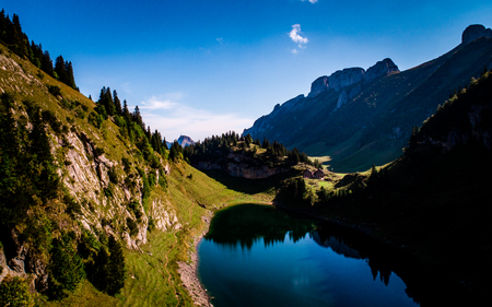 aerial view of deep blue mountain lake in swiss alps with house, switzerland alpstein