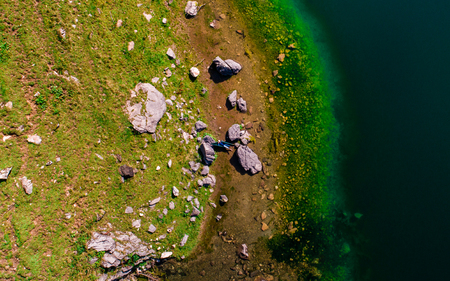 aerial top down view of guy chilling in a hammock between two stones at a mountain lake, switzerland Archivio Fotografico - 120999317