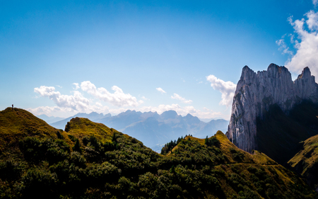 person standing on top of a mountain summit watching on speical rock formation switzerland alpstein