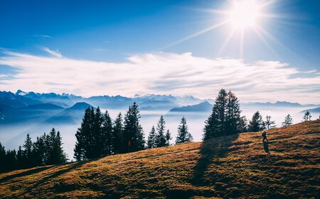 aerial view of couple hiking at beautiful scenery with fog covered mountains and lake, relationship goals in the swiss alps on rigi monutain sunny