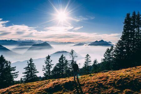 aerial view of guy looking at mountain scenery in the swiss alps during late autumn, colored pinetrees and blue Lake Lucerne covered in fog seen from rigi switzerland