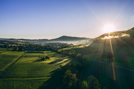 aerial shot of beautiful green field with morning dew during sunny day in the countryside of switzerland, peaceful relaxing drone shot Archivio Fotografico