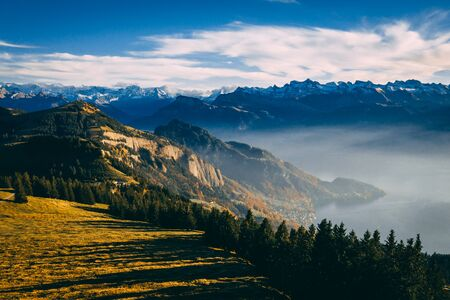 aerial view of mountain scenery in the swiss alps during late autumn, colored pinetrees and blue Lake Lucerne seen from rigi switzerland sunny