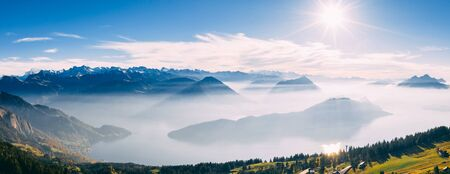 drone view over snow covered mountains during autumn, aerial view over swiss alps with lake in fog covered, rigi switzerland sunny