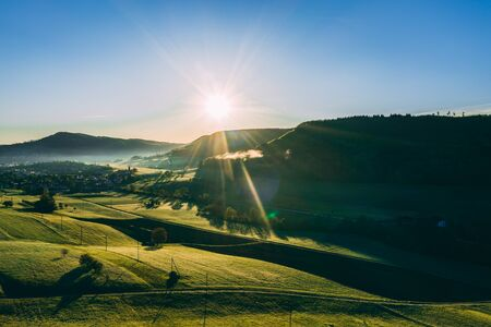 aerial view over agricultural fields during morning sun in the countryside of switzerland, peaceful relaxing drone shot Archivio Fotografico - 131919854