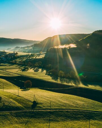 aerial view over agricultural fields during morning sun in the countryside of switzerland, peaceful relaxing drone shot