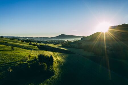 relaxing aerial shot of countryside village in switzerland during morning sun, beautiful sunny day with very green agricultural fields Archivio Fotografico
