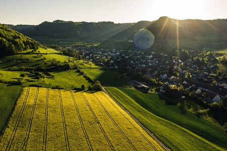 aerial overview of countryside during golden hour with yellow flowers in a small village, Field of rapeseed in full flower, spring time in countryside switzerland Archivio Fotografico