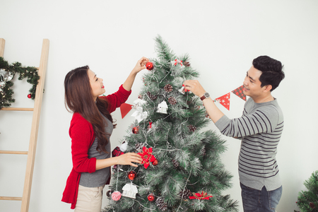 Christmas Asian Couple. Happy Smiling Family at home celebrating. New Year People