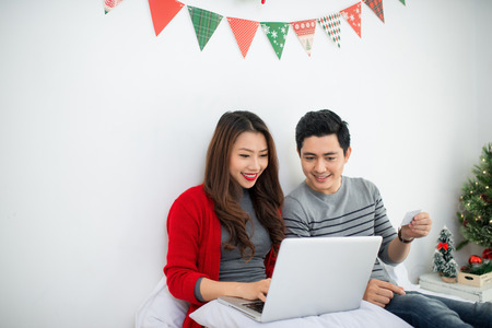 Christmas. Asian Couple using digital tablet at home celebrating New Year.