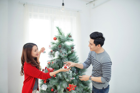 Christmas Asian Couple.Happy Smiling Family at home celebrating.New Year People Stock Photo