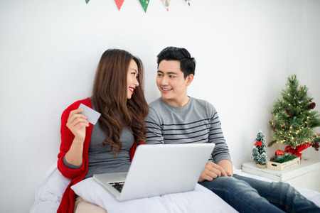 Christmas. Asian Couple Shopping Online at home celebrating New Year.