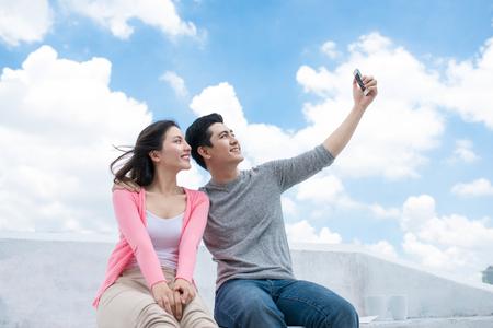 Jonge mooie vrouw en Aziatische man lachen tegen de donkere blauwe hemel met wolken