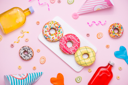 Party. Different colourful sugary round glazed donuts and bottles of drinks on pink background. Stock Photo