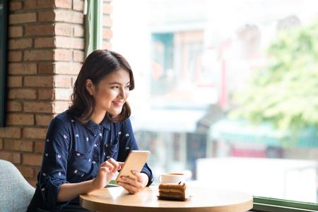 Mooie leuke Aziatische jonge onderneemster in de koffie, het gebruiken van mobiele telefoon en het drinken koffie het glimlachen