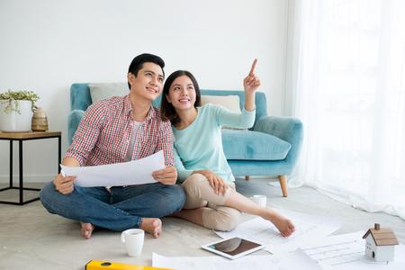 Aantrekkelijk jong Aziatisch volwassen paar die nieuw huisontwerp plannen.