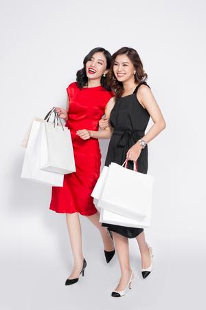 Twee gelukkige aantrekkelijke jonge vrouwen met boodschappentassen op witte achtergrond
