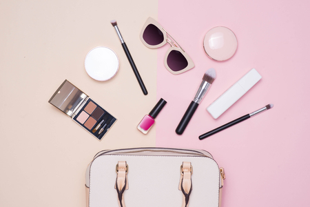 Flat lay of female fashion accessories and white handbag on pastel color background with copyspace Banco de Imagens