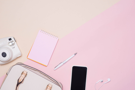 Flat lay of female fashion accessories and white handbag on pastel color background with copyspace Фото со стока