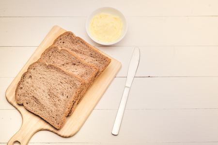Close-up of slice of toast bread with butter on wood table Stock Photo