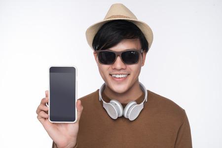 Slimme toevallige Aziatische man op stoel zitten, met smartphone scherm in studio achtergrond