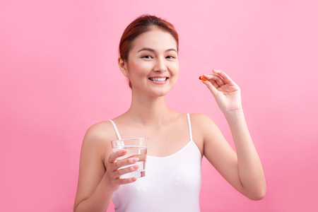 Young asian beauty young woman eating pills and drinking water on pink background.