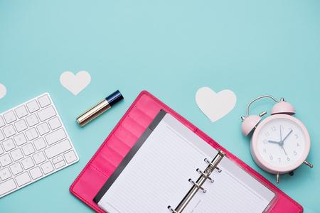 母の日の概念。女性のオフィスの机の上のギフト ボックスとピンクのバラ。コピー スペースのノートブックを開く。 写真素材