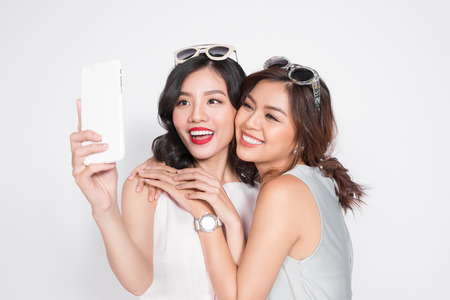 Portrait of two beautiful asian fashionable women taking selfie Фото со стока