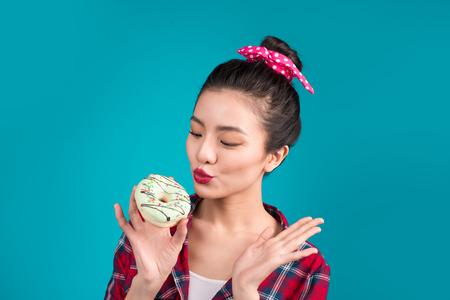 レトロなうれしそうな女性を楽しむお菓子、デザートの立っている青い背景の上。