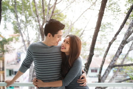 Couple in love sharing genuine emotions and happiness, hugging on the balcony