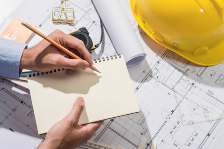 architect: Working on blueprints. Construction project with hands writing on notebook.