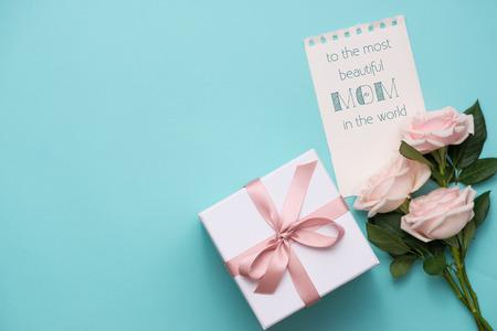 Moederdag concept. Boeket van roze rozen met geschenkdoos en lippenstift. Blanco papier notitie voor kopie ruimte. Stockfoto - 77794540