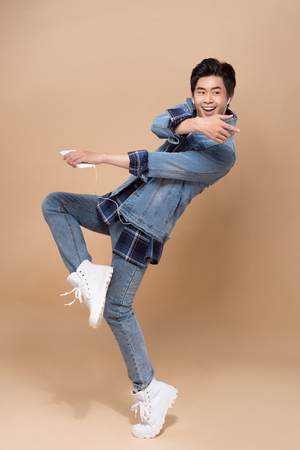 Cheerful elegant young handsome asian man jumping. Cool fashion male model.