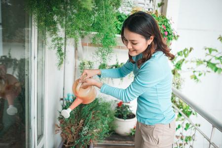 Mulher que balança a planta no recipiente no jardim da varanda