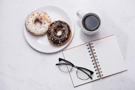 Bureau met dessert en koffie. Cake donuts met een kopje espresso op marmeren tafelblad. Stockfoto