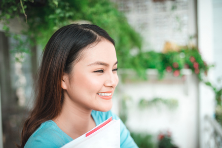 novel: Asian smiling woman reading novel book at home.