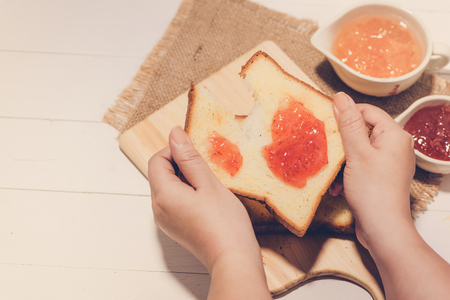 Asian woman eating bread with strawberry jam for breakfast. Focus on hands.