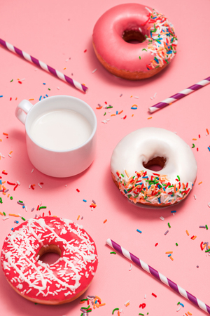 Donuts with icing and milk on pastel pink background. Sweet donuts. Stock Photo