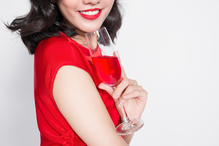 Cropped images of young celebrating asian woman in red dress holding wine glass.