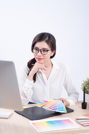 Graphic designer at work. Asian woman sitting on desk.