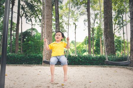 Leuk weinig Aziatische jongen in een park op een aardige dag in openlucht