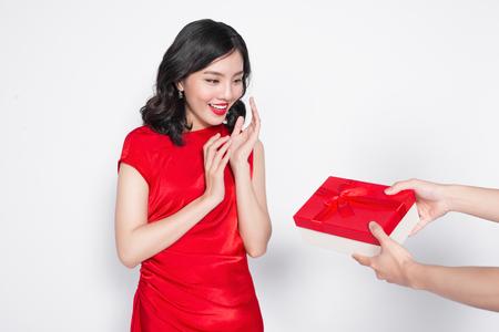 Mooie gelukkige Aziatische vrouw in rode kleding die giftdoos ontvangt Stockfoto