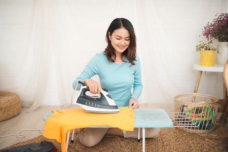Happy young asian woman ironing clothes sitting on floor at home. Stock Photo