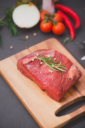 Raw beef on a cutting board  with spices and ingredients for cooking. Stock Photo - 78094990