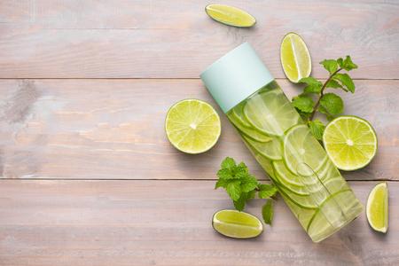 Detox gaf water met kalk en munt in een sportfles, met plakjes limoen.