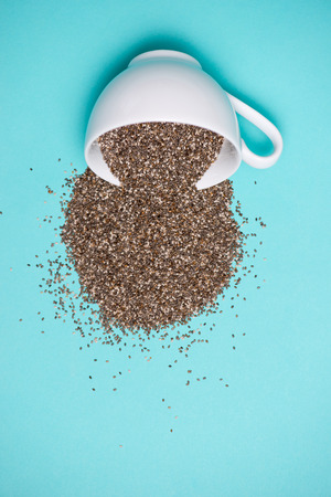 Nutritious chia seeds in cup on light blue background. Stock Photo