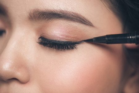Close-up portrait of beautiful girl touching black eyeliner to her eyelid with closed eyes.